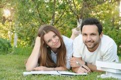 Пары молодых студентов studing в парке кампусом Стоковое Фото