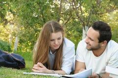 Пары молодых студентов studing outdoors Стоковая Фотография RF