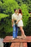 Пары молодых любовников обнимая на пристани Стоковые Фотографии RF