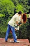 Пары молодых любовников обнимая на пристани Стоковое Фото