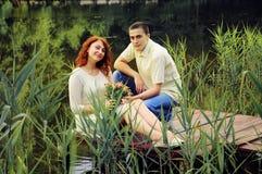 Пары молодых любовников обнимая на пристани Стоковое Изображение