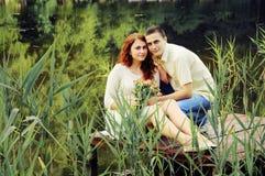 Пары молодых любовников обнимая на пристани Стоковое Изображение RF