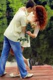 Пары молодых любовников обнимая на пристани Стоковая Фотография RF