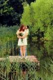 Пары молодых любовников обнимая на пристани Стоковые Изображения