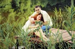 Пары молодых любовников обнимая на пристани Стоковое фото RF