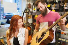 Пары музыкантов с гитарой на магазине музыки Стоковое Изображение
