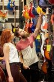 Пары музыкантов с гитарой на магазине музыки Стоковое Изображение RF