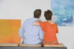 Пары наблюдающ картиной в художественной галерее стоковые фотографии rf
