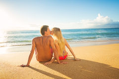Пары наблюдая заход солнца на тропических каникулах пляжа Стоковые Изображения