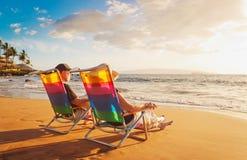 Пары наслаждаясь заходом солнца на пляже стоковые фотографии rf