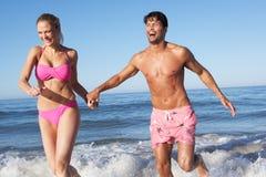Пары наслаждаясь праздником пляжа Стоковая Фотография