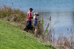 Пары наслаждаясь удить на озере Greenfield, Вирджинии, США Стоковая Фотография RF