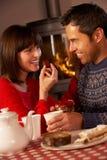 Пары наслаждаясь чаем и тортом Cosy пожаром журнала Стоковое Изображение RF