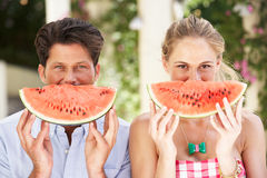 Пары наслаждаясь ломтиками арбуза Стоковое Фото