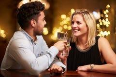 Пары наслаждаясь вечерними напитками в баре Стоковая Фотография RF