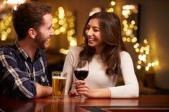 Пары наслаждаясь вечерними напитками в баре Стоковое Изображение