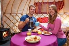 Пары наслаждаясь завтраком пока располагающся лагерем в традиционном Yurt Стоковое Изображение RF
