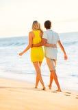 Пары наслаждаясь заходом солнца на пляже Стоковое Изображение