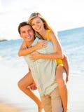 Пары наслаждаясь заходом солнца на пляже Стоковая Фотография