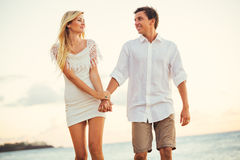 Пары наслаждаясь заходом солнца на пляже Стоковая Фотография RF