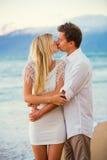 Пары наслаждаясь заходом солнца на пляже Стоковые Фото