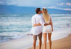 Пары наслаждаясь заходом солнца на пляже Стоковые Изображения RF