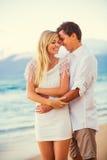 Пары наслаждаясь заходом солнца на пляже Стоковое Фото