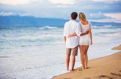 Пары наслаждаясь заходом солнца на пляже Стоковые Изображения