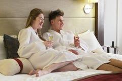 Пары наслаждаясь питьем в гостиничном номере Стоковое Фото