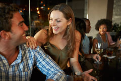 Пары наслаждаясь питьем на баре с друзьями Стоковое Изображение