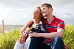 Пары наслаждаясь праздником в дюне пляжа Стоковые Изображения