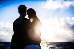 Пары наслаждаясь романтичным заходом солнца на пляже Стоковые Фото