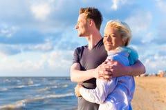 Пары наслаждаясь романтичным заходом солнца на пляже Стоковая Фотография RF