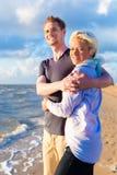 Пары наслаждаясь романтичным заходом солнца на пляже Стоковая Фотография