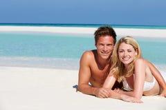 Пары наслаждаясь праздником пляжа Стоковые Изображения