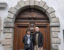 Пары на каникулах перед богато украшенной деревянной дверью с knocker, Cesky Krumlov, чехией стоковое фото