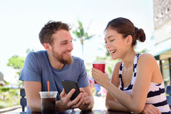 Пары на кафе смотря умные изображения app телефона Стоковая Фотография