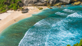 Пары на красивом Atuh приставают к берегу с белыми длинными волнами, Nusa Penida, Бали, Индонезией Стоковое фото RF