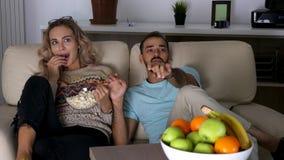 Пары на кресле в живущей комнате смотря страшный фильм ужасов на ноче видеоматериал