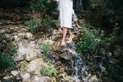 Пары на предпосылке потока горы нога идя через водопад, springwater стоковое изображение