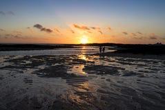 Пары на пляже на заходе солнца Стоковые Фотографии RF