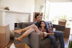 Пары на софе принимая пролом от распаковывать на Moving день Стоковое Фото