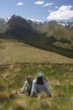 Пары на траве смотря горы Стоковая Фотография RF