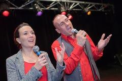 Пары на этапе поя с микрофонами стоковая фотография