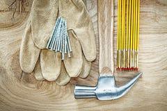Пары ногтей молотка с раздвоенным хвостом метра защитных перчаток деревянных на древесине Стоковая Фотография