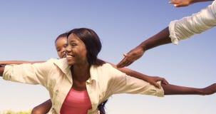 Пары нося их детей на их задней части сток-видео