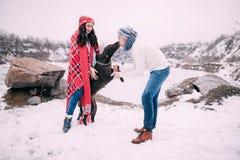 Пары обернутые в красной шотландке с собакой во время зимы идут Поцелуи человека Yong собаки Стоковая Фотография RF