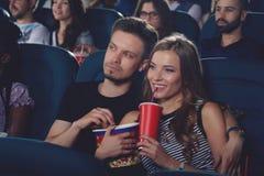Пары обнимать в коле кино выпивая и еды попкорна Стоковые Изображения