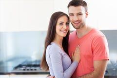 Пары обнимая в кухне Стоковые Изображения
