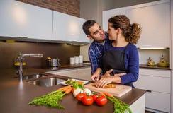 Пары обнимая и подготавливая овощи в Стоковое Изображение RF